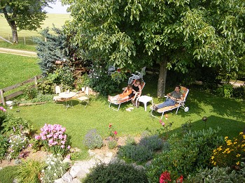 Ein großzügiger Garten mit schattenspendenden Bäumen.